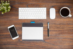 Illustrator desk seen from above. High angle view of the workspace of an illustrator or retoucher. A keyboard, pen tablet, smartphone and some coffee on a wooden royalty free stock photography