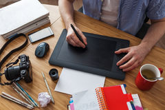 Illustrator draws a sketch. Workplace of designer. Graphic tablet surrounded by phone, camera, pencils and books Royalty Free Stock Image