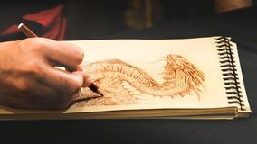 Illustrator hand drawing dragons sketchbook scratch book. Dozza, Italy, 23 Sep 2018 - An illustrator hand is drawing a dragon on a sketchbook notepad stock photography