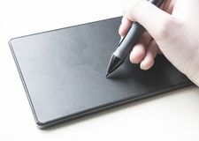 Illustrator at work with pen and tablet. An illustrator makes a digital sketch with a pen and tablet set up stock photo