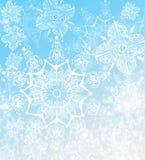 Illustrazione dei fiocchi di neve su una priorità bassa blu-chiaro illustrazione di stock