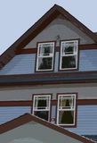 Illustrazione del lato di una casa con quattro finestre tutta di Posterize con le tende immagine stock libera da diritti