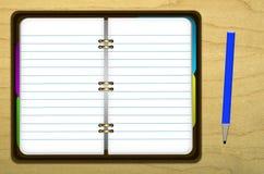 Illustrerad anteckningsbok och blyertspenna på den wood tabellen Arkivbilder