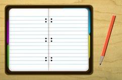 Illustrerad anteckningsbok och blyertspenna på den wood tabellen Royaltyfri Bild