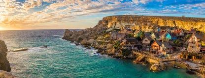 IlMellieha,马耳他-著名Popeye村庄的全景地平线视图船锚海湾的在日落 免版税库存图片