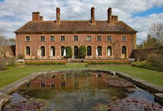 ILMINSTER, SOMERSET, ENGLAND - APRIL 15TH 2012: An English stately home sits behind an ornamental pond royalty free stock photo