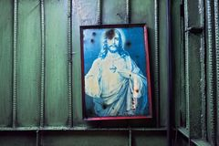 Framed picture of Jesus Christ hanging on a metal wall. Iloilo, Iloilo Province, Philippines: Framed picture of Jesus Christ hanging on a metal wall near the stock image