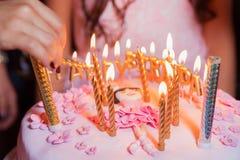 Ils brûlent des bougies sur l'anniversaire Gâteau d'anniversaire brouillé avec des bougies sur le fond de lumières Images stock