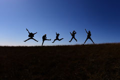 Ils sautent tout en marchant sur une colline Image libre de droits