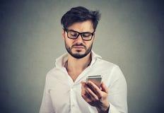 Ilsken äcklad man som använder smartphonen arkivbild