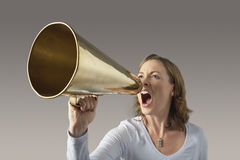 Ilsken affärskvinna Shouting Through Megaphone Royaltyfri Bild