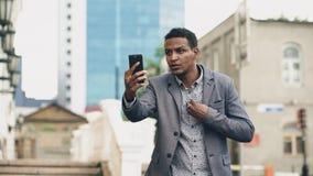 Ilsken affärsman för blandat lopp som har online-video pratstund i affärskonferens genom att använda smartphonen arkivbilder