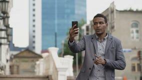 Ilsken affärsman för blandat lopp som har online-video pratstund i affärskonferens genom att använda smartphonen arkivfilmer