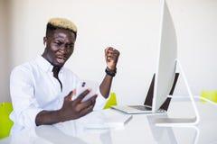 Ilsken affärsman i spänningen som arbetar och talar på mobiltelefonen på kontorsskrivbordet arkivfoto