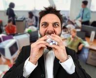 Ilsken affärsman, medan äta klumpa ihop sig papper i regeringsställning Arkivfoton