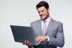 Ilsken affärsman som använder bärbara datorn arkivbilder