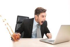Ilsken affärsman som arbetar på hans bärbar datordator royaltyfri bild
