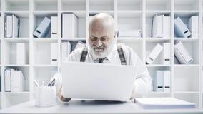 Ilsken affärsman som bryter hans bärbar dator arkivfoton