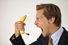 Ilsken affärsman som ropar på bananen Royaltyfri Foto