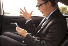 Ilsken affärsman som ropar på telefonen med gest Arkivbild