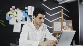 Ilsken affärsman som ser till kameran som sitter i hans arbetsplats stock video