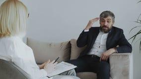 Ilsken affärsman som talar om hans problem med den kvinnliga psykologen i hennes kontor arkivfilmer