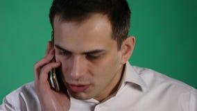 Ilsken affärsman som talar på mobiltelefonen som isoleras över grön bakgrund stock video