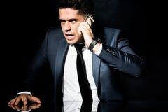 Ilsken affärsman som talar på telefonen royaltyfri bild