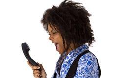 Ilsken afrikansk amerikankvinna med telefonluren arkivbild