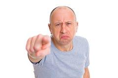Ilsken baldheaded man som in pekar till kameran och le arkivbild