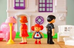 Ilsken begreppsbild av föräldern som är upptagen eller och barnet i mitt framme av små plast- leksakdockor (mannen, kvinnlig, bar arkivfoton