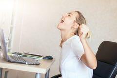 Ilsken blond kvinna som arbetar på den hemmastadda bärbara datorn och skriker henne rubbning för ` s Frilans hemmastatt begrepp f royaltyfria foton