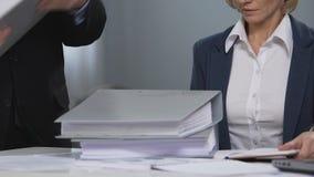 Ilsken chef som framme kastar mappar av coworkeren, kvinnarätter i affär arkivfilmer