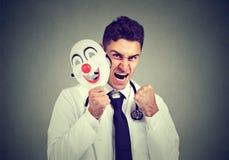 Ilsken doktor som tar av att le maskeringen royaltyfri foto
