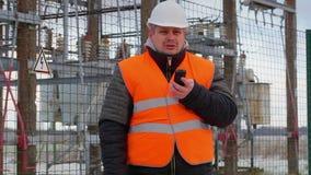 Ilsken elektroingenjör som talar på mobiltelefonen i avdelningskontor arkivfilmer