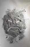 Ilsken emoticon som göras av askaen Arkivfoto