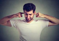 Ilsken förargad man som pluggar hans öron med fingrar fotografering för bildbyråer