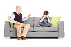 Ilsken farfar som ropar på hans brorson som placeras på en soffa Arkivfoton