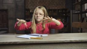 Ilsken flicka som hemma kastar böcker ut ur tabellen lager videofilmer