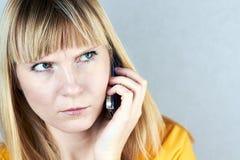 Ilsken flicka som talar på hennes mobiltelefon Fotografering för Bildbyråer