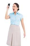 Ilsken flott affärskvinna som ropar på hennes smartphone royaltyfri bild