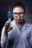 Ilsken galen asiatisk doktor med en injektionsspruta fotografering för bildbyråer