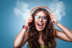 Ilsken galen flicka i hörlurar som lyssnar till musik arkivbild