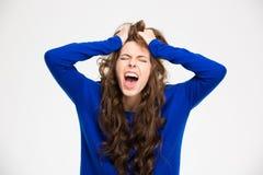 Ilsken galen ung kvinna med långt skrika för lockigt hår Fotografering för Bildbyråer