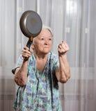 Ilsken gammal kvinna med en panna Royaltyfri Fotografi