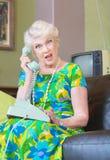 Ilsken hög kvinna på telefonen Arkivbild