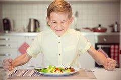 Ilsken hungrig pojke som bankar hans näve på tabellen royaltyfri foto