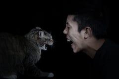 Ilsken katt och man Arkivfoto