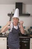 Ilsken kock som rymmer en stor kniv Fotografering för Bildbyråer