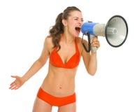 Ilsken kvinna i baddräkt som ropar till och med megafonen Royaltyfri Fotografi